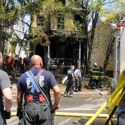 Firefighters from the City of Poughkeepsie Fire Department clean up after putting out a fire at 315 Church St. in the City of Poughkeepsie.