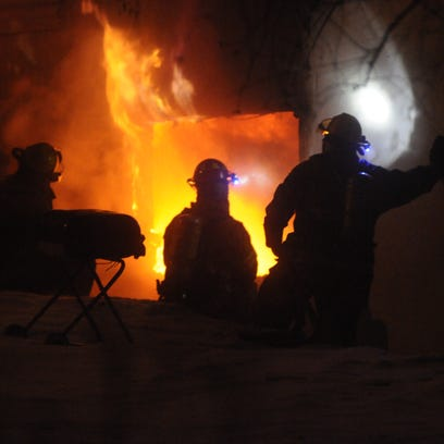 Sauk Rapids fire chief Jason Fleming watches as firefighters enter a house Saturday night.