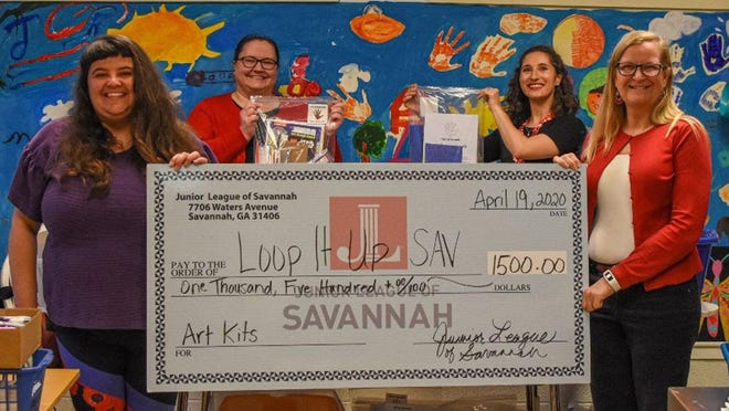 Loop It Up Executive Director Molly Lieberman accepts a check from Junior League of Savannah members Dianne Talcott, Mary Tyler Paradise and Erin Curran.