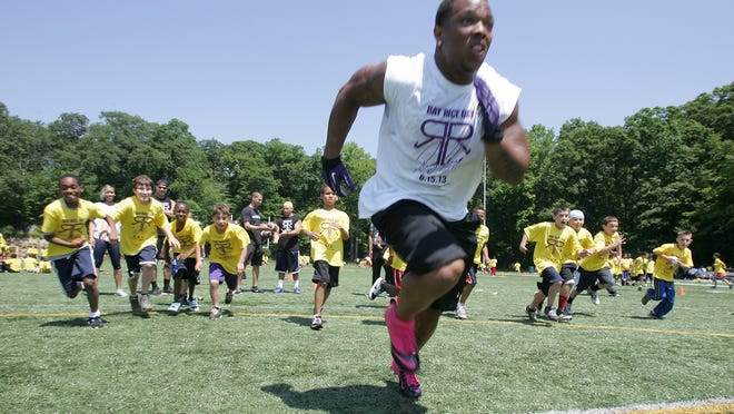 Baltimore Ravens running back, Ray Rice, races with the kids during Ray Rice day at the Joseph F. Fosina Field in New Rochelle on June 15, 2013.