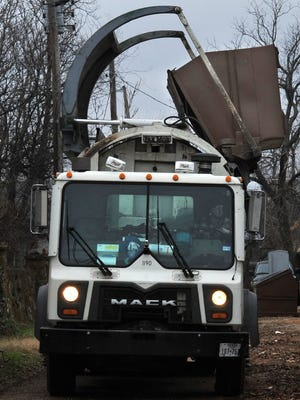 A Wichita Falls sanitation truck empties an alleyway dumpster near Monroe Street.