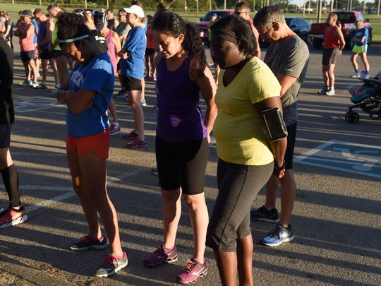 Members of Team 13 unite in prayer before training at Wesselman Park in Evansville Tuesday.  The team of hundreds of runners are using the training program to prepare for the Evansville Half Marathon in October.