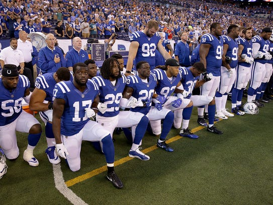 Several Indianapolis Colts players kneel during the