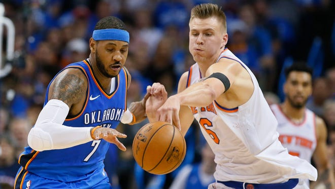 Oklahoma City Thunder forward Carmelo Anthony (7) and New York Knicks forward Kristaps Porzingis (6) reach for the ball in the second quarter of an NBA basketball game in Oklahoma City, Thursday, Oct. 19, 2017.