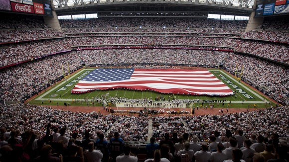 A large American flag is unfurled on the field before the Colts played the Texans at Houston's Reliant Stadium on Sept. 11, 2011.