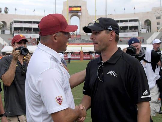 Southern California coach Clay Helton (left) shakes