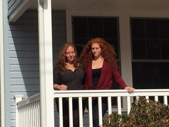 Teresa Keefe, left, and her daughter Shayla stand on the front porch of their rebuilt home in Belmar.