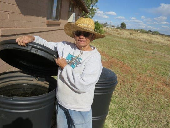 Sister Kathy Cook shows a rain barrel where water is