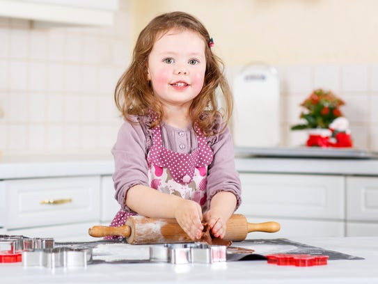 A little girl decorating holiday cookies in the kitchen.