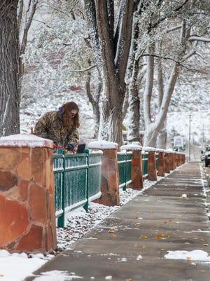 A Cedar City employee clears snow off the fence surrounding Main Street Park following the first snowfall of the season, Thursday, Nov. 17, 2016.