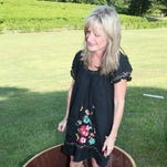 A guest tries her hand at stomping grapes at last year's grape stomp at Landry Vineyards. This year's Blanc Du Bois Stomp Fest is Saturday.