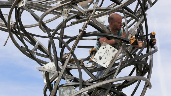 "Artist Deveren B. Farley installs his ""Silly Symphony"" metal sculpture Thursday in the roundabout at the intersection of Main Street and 200 North in St. George. It will be part of this year's new Art Around the Corner exhibit."