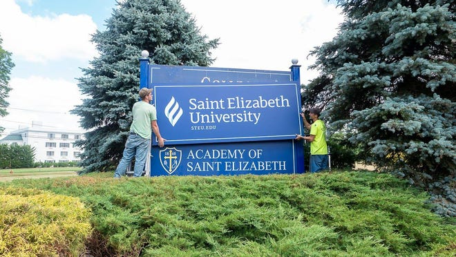 Workers replace the College of Saint Elizabeth entry sign with its new name and status: Saint Elizabeth University. The Academy of Saint Elizabeth private school also is located on the campus in Florham PArk and Morris Township.