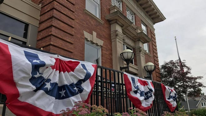 The Macomb Public Library is decorated with patriotic flags on the railinga and paper hearts on the windows. It is currently closed to the public.