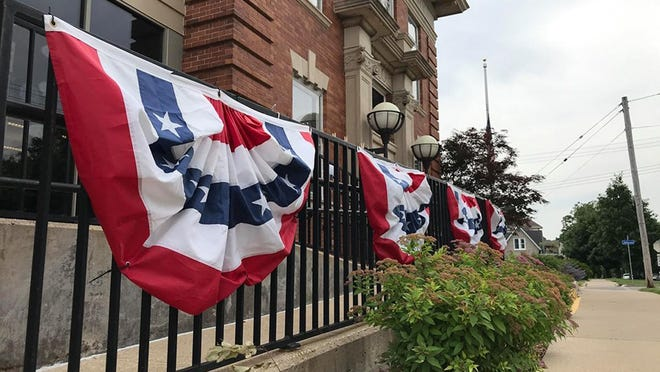 The Macomb Public Library, seen here with patriotic decorations on the front rail, will begin offering curbside pickup on July 1.