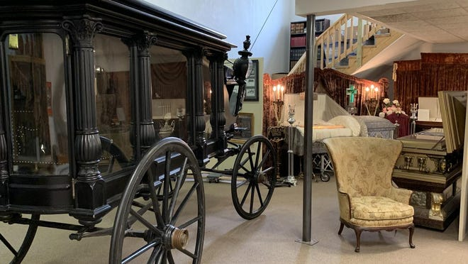 Replica of horse-drawn hearse and funeral coffins.