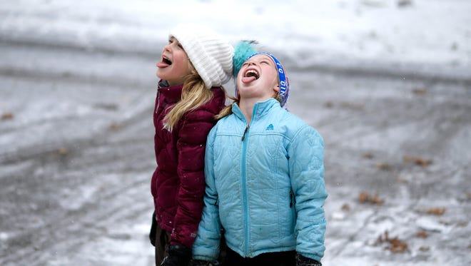 Neighbors Lucy McGee, 9, and Lauren Bower, 10, catch snowflakes on their tongues in the Hyde Park neighborhood of Cincinnati on Thursday, Jan. 5, 2017.