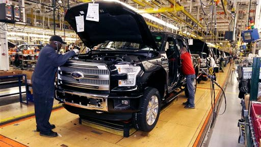 In this Nov. 6, 2014 photo, the new Ford F-150 truck is assembled at the Rouge Truck Plant in Dearborn, Mich. Buoyed by a resurgent economy, holiday sales, cheap gasoline and low interest rates, Americans headed to car dealers in droves in December, pushing full-year sales to what's likely to be the highest level since 2006. (AP Photo/Carlos Osorio)