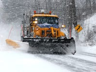 A New York State Department of Transportation plow scrapes snow off Route 376 in the Town of Poughkeepsie.