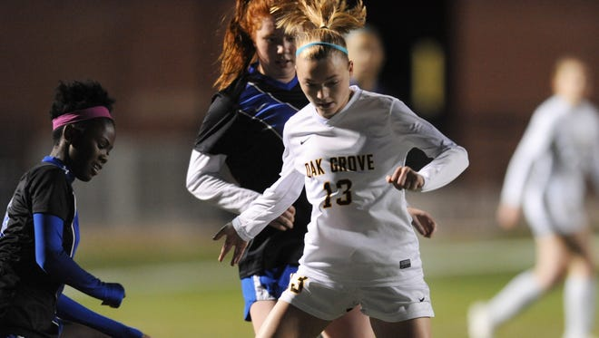 Oak Grove's Maggie Starns takes the ball past Meridian High School defenders Tuesday at Oak Grove.