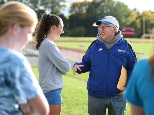 Dave Hennessey, cross country coach at Penfield High School, talks with senior Tori Fahrenholz as they head out for their run at the school on Oct. 14, 2015.