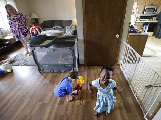 Mindi Piasecki watches as her children, Adam, 1, and Tess, 3, play in the living room while Mark Piasecki gets lunch ready on June 14 at their home in Neenah.