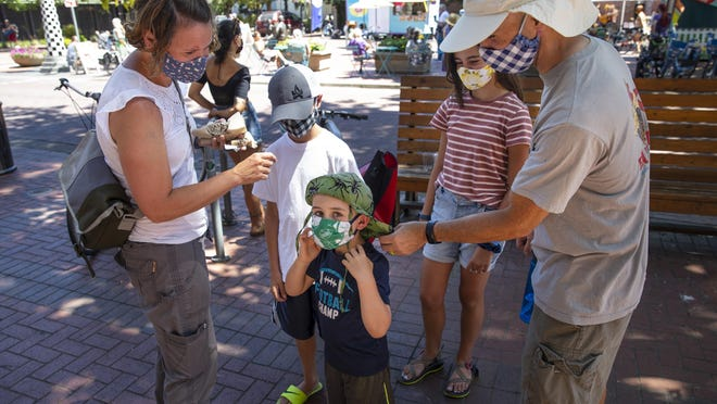 Four-year-old Rory Zito adjusts his mask as he visits downtown Eugene with his family. The Zito family, all accessorized with custom homemade masks, were visiting Oregon from Utah this week. [Chris Pietsch/The Register-Guard] - registerguard.com