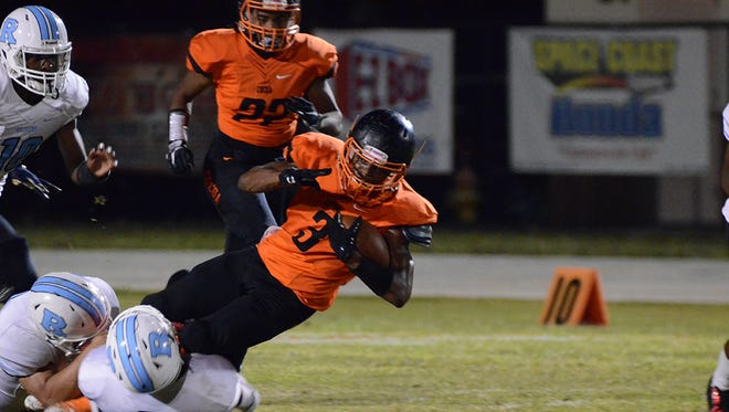 Javian Hawkins is brought down by a pair of Rockedge Raiders defenders.(photo by Tony Dees/Florida Today)