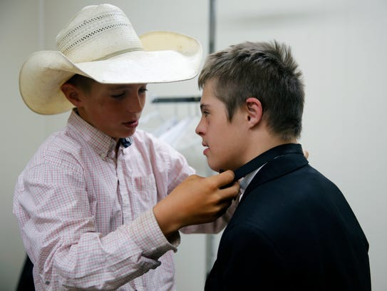 Cash Carruth, 11, helps his brother, Joshua Carruth,