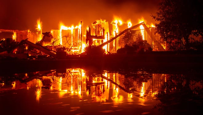 A burning home is reflected in a pool during the Carr fire in Redding, Calif., on July 27, 2018.