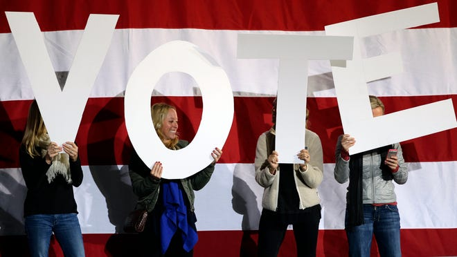 "Women hold up signs spelling ""vote"" on a stage being prepared for a speech by President Barack Obama at a campaign rally at the Community College of Aurora, in Denver, Sunday, Nov. 4, 2012."
