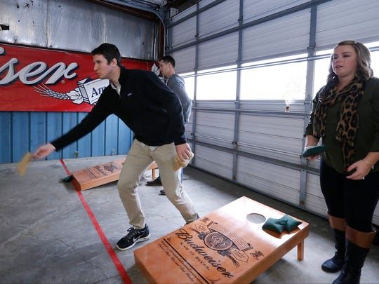 Dan Cwieka, of New Jersey, and Margaret Coseo, of Elmira, compete in the cornhole tournament at the Finger Lakes Beer Festival Saturday.