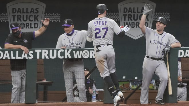 Colorado Rockies' Trevor Story (27) is congratulated at the dugout after his home run in the fourth inning of win over the Texas Rangers on Sunday in Arlington.