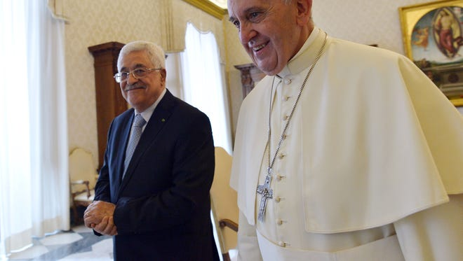 Pope Francis walks next to Palestinian leader Mahmoud Abbas during an audience at the Vatican, May 16, 2015.