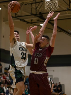 Colts Neck's Brandan Clarke goes up with shot against Matawans Mike Dunne during first half action. Matawan boys basketball vs Colts Neck in SCT game at Colts Neck, NJ. on February 13, 2017.
