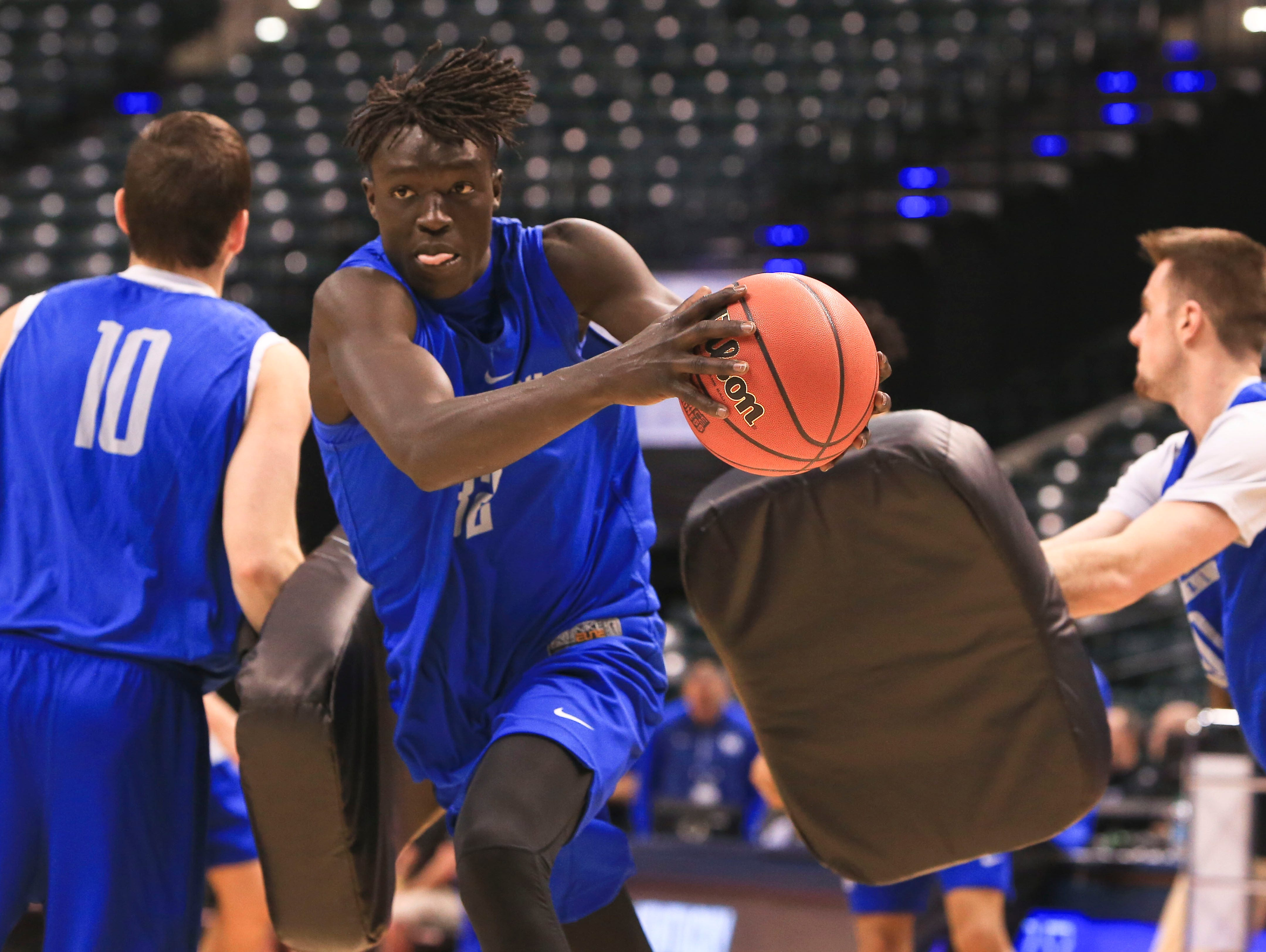 Kentucky's Wenyen Gabriel powers through a drill as Jonny David, left, and Dillon Pulliam use pads to simulate pressuring defense during practice Thursday afternoon at Bankers Life Fieldhouse before the start of the team's NCAA tournament play. The team takes on Northern Kentucky Friday evening at 9:40 pm.