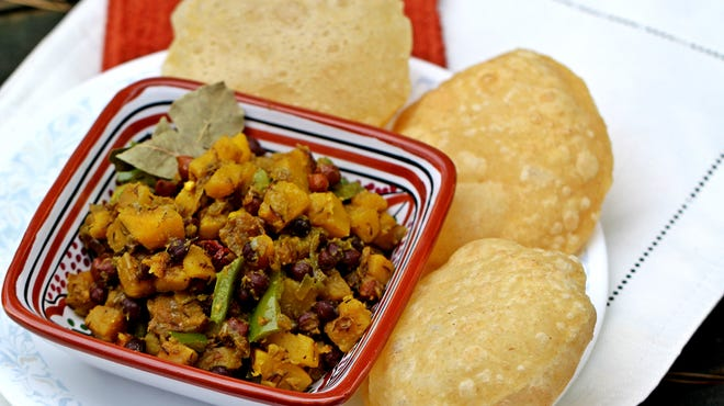 """Spiced Pumpkin Squash with Chickpeas is served with Luchi, Deep-Fried Puffy Breads, adapted from """"The Bengali Five Spice Chronicles"""" by Rinku Bhattacharya."""