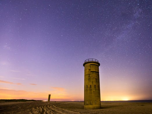 Fire control control towers along the beach in Cape Henlopen State Park near Gordon Pond are illuminated by the distant light of Rehoboth and Dewey Beaches on Saturday night, July 26, 2014. Along the horizon, glow from Cape May, N.J. (right) can be seen beneath the dusty band of the Milky Way in the sky.