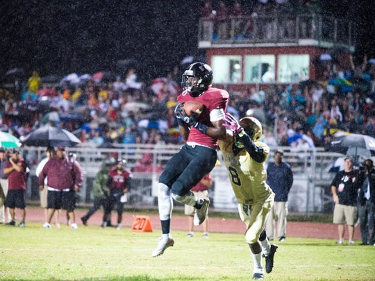 Chiles' John Mitchell catches a touchdown in the rain during Lincoln's 8-7 win in a district tiebreaker three years ago.