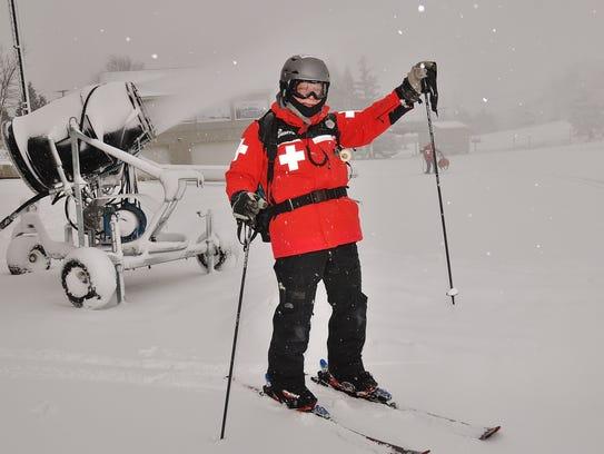 Ski patroller Mike Brady raises a ski pole to cheer