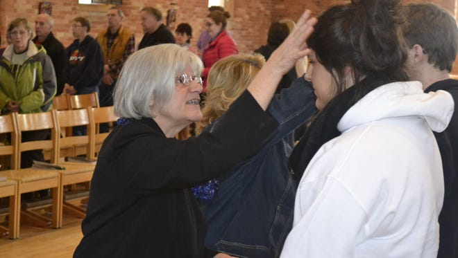 Sister Laura Zelten, left, administers ashes during an Ash Wednesday service at St. Norbert College's Old St. Joseph Church in De Pere this week.