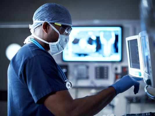 A surgeon looks at a patient's vitals through an operating room monitor.