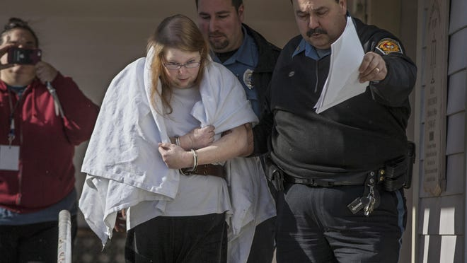 """Sara Packer, center, handcuffed, the adoptive mother of Grace Packer, was led out of District Court in Newtown, Pa., Sunday, Jan. 8, 2017, by Pennsylvania Constables and taken into custody. Packer, whose teenage daughter's dismembered remains were found in the woods last fall, has been charged along with her boyfriend Jacob Sullivan with killing the girl in a """"rape-murder fantasy"""" the couple shared, a prosecutor said Sunday. (Michael Bryant/The Philadelphia Inquirer via AP)"""