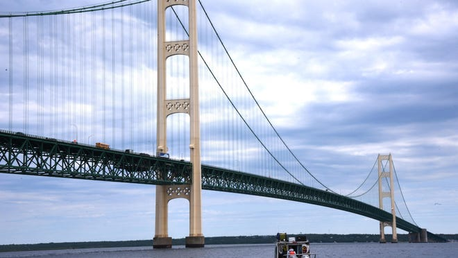 Oil pipeline operator Enbridge moves under the Mackinac Bridge on their way to inspect their controversial Line 5 under the Straits of Mackinac in this June 8, 2016 file photo. Michigan Attorney General Bill Schuette is suing an Escanaba-based company whose boat allegedly dropped an anchor this month that ruptured a pair of power cables and dented Enbridge's Line 5 oil pipeline under the Straits of Mackinac, his office said Thursday.