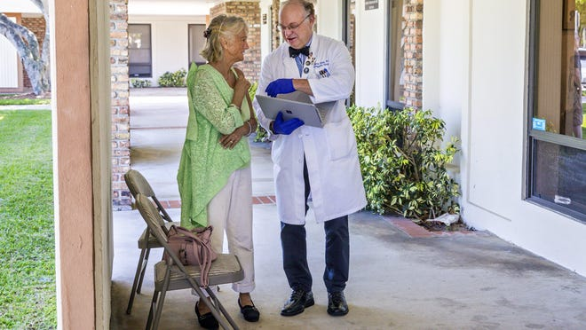 Orthopedic surgeon Dr. Ross G. Stone examines patient Shirley Letouneau in the breezeway outside his office in Atlantis.
