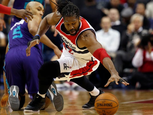 Washington Wizards forward Nene (42), from France, dives away from Charlotte Hornets guard Jannero Pargo (5), for the loose ball in the first half of an NBA basketball game, Monday, Feb. 2, 2015, in Washington. (AP Photo/Alex Brandon)