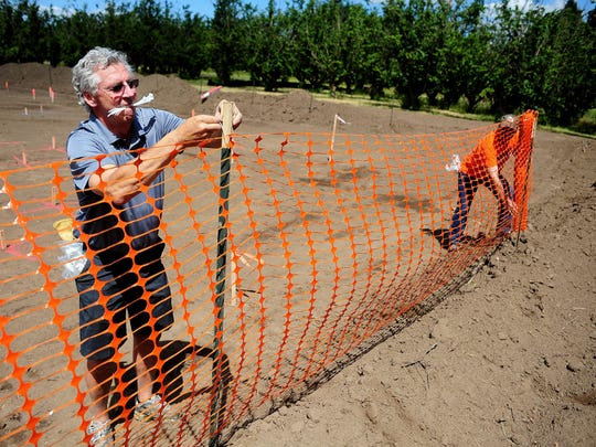 Kim Girouard, left, and Mark Caillier install construction fencing as pre-work begins on the Keizer Big Toy community Build at Keizer Rapids Park, on Thursday, in Keizer.