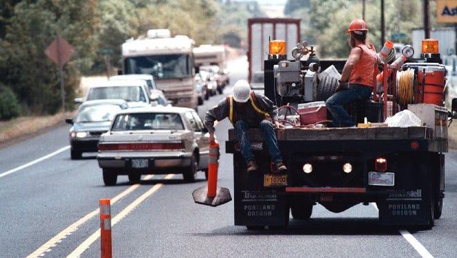 ODOT workers pick up barriers on Highway 22 near Salt Creek.