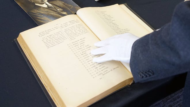 Wearing a protective glove, Robin Peaslee Dougall, the grandson of U.S. Army Maj. Amos Peaslee, shows off his grandfather's draft copy of the Treaty of Versailles.