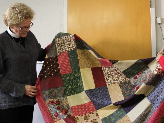 Karen Boyd, left, and Sarah Shelby with another finished quilt, this one a patchwork pattern, at Episcopal Church of the Heavenly Rest.